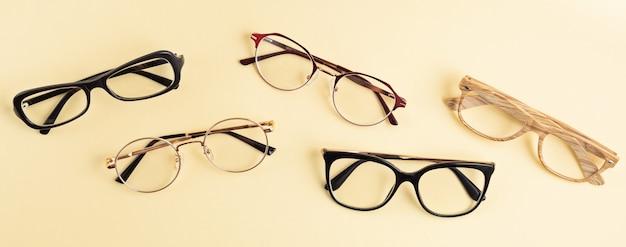 Banner con colección de anteojos sobre pared pastel. tienda de óptica, selección de gafas, examen ocular, examen de la vista en el óptico, concepto de accesorios de moda. vista superior, endecha plana
