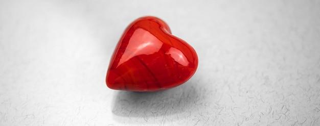 Banner corazón rojo solitario sobre un fondo gris simple, concepto de amor, espacio de copia