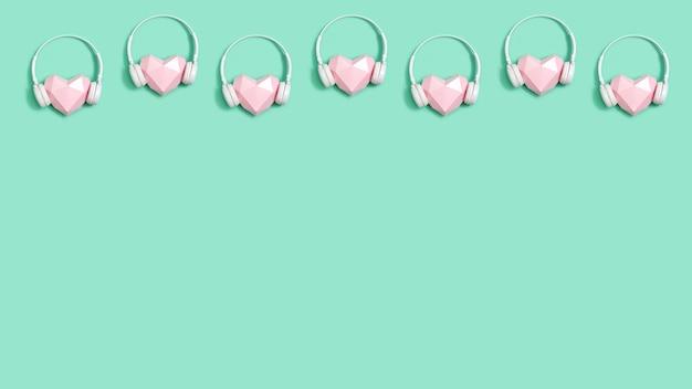 Banner creativo con forma de corazón de papel poligonal rosa tierno en auriculares blancos concepto de música