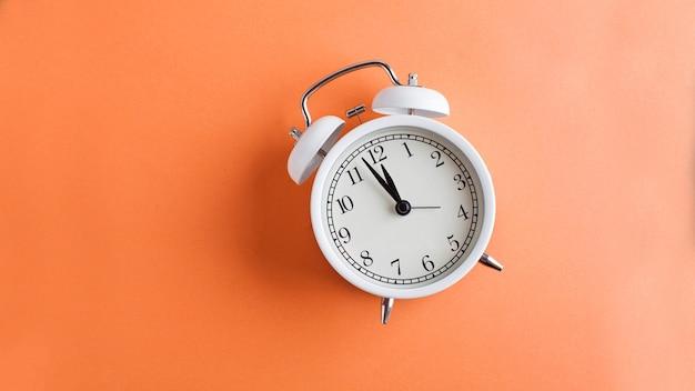 Banner despertador blanco sobre una superficie de color naranja