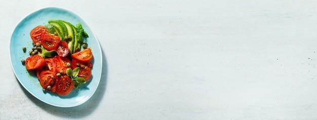 Banner de ensalada de verano con tomates maduros y aguacate con alcaparras en una placa azul sobre la mesa