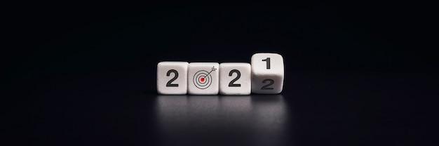 Banner de feliz año nuevo 2022 con concepto de objetivo y éxito empresarial. volteo de bloques de dados negros para cambiar números de 2021 al nuevo año 2022 sobre fondo oscuro, estilo moderno y minimalista.