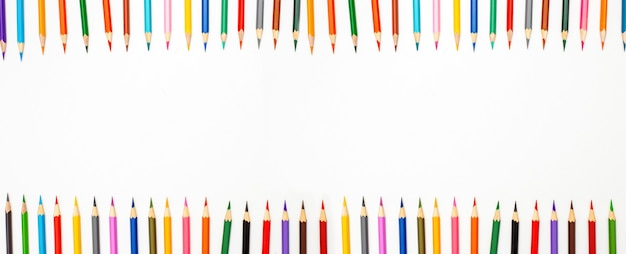 Banner de lápices de colores de marco en una fila con la parte superior sobre una superficie blanca.