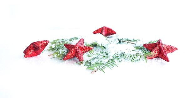Banner de navidad estrellas rojas con brillo en ramas de abeto cubiertas de nieve sobre un fondo blanco
