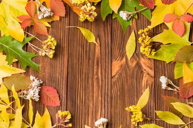 Banner de otoño con coloridas hojas de árboles y flores secas en madera marrón
