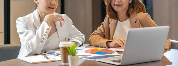 Banner, página web o plantilla de portada de dos empresarias asiáticas que trabajan con la empresa asociada a través de una computadora portátil tecnológica en la sala de reuniones moderna, oficina o espacio de trabajo, concepto de socio y colega