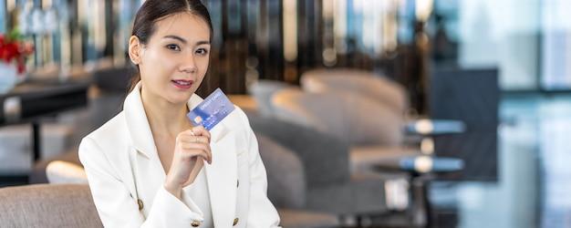 Banner, página web o plantilla de portada de retrato mujer asiática con tarjeta de crédito para compras en línea