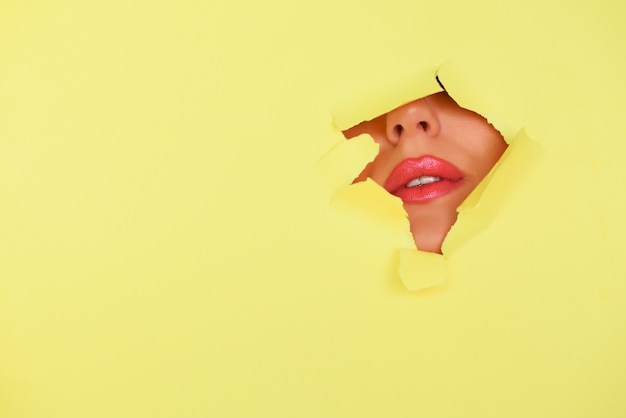 Banner de publicidad salón de belleza con espacio de copia. vista de labios brillantes con brillo a través del agujero en el fondo de papel amarillo.