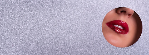 Banner de publicidad salón de belleza con espacio de copia. vista de labios brillantes con brillo a través del agujero en el fondo de papel de plata.