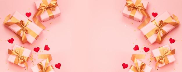 Banner de san valentín cajas de regalo rosa con lazo de oro con forma de amor rojo sobre fondo rosa. lay flat, vista superior, espacio de copia.
