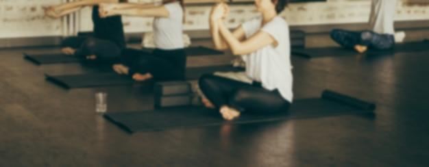 Banner de sitio web borroso con gente haciendo yoga en estudio de yoga