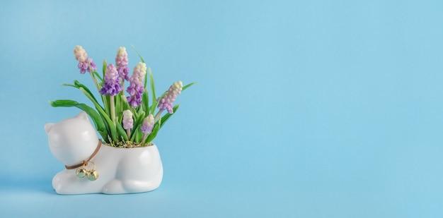 Banner de tarjeta de felicitación, composición con gato y flores de primavera sobre fondo azul con espacio de copia