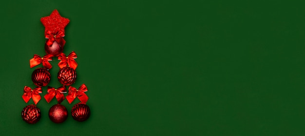 Banner de tarjeta de felicitación para navidad y año nuevo en un fondo verde con un árbol de navidad minimalista hecho de bolas rojas de navidad y lazos rojos. año nuevo chino.