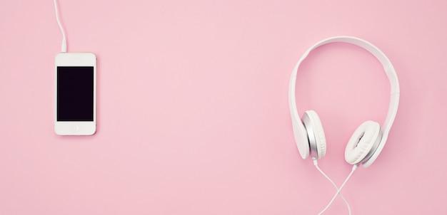 Banner con el teléfono celular y los auriculares sobre el fondo rosa. música, entretenimiento, listas de reproducción en línea.