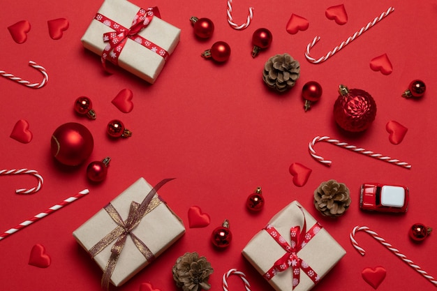 Banner de vacaciones de navidad y año nuevo con regalo artesanal, conos de abeto y coche sobre un fondo rojo. vista plana, vista superior
