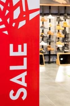 Banner de venta rojo brillante en el sensor de puerta antirrobo en la entrada del centro comercial minorista