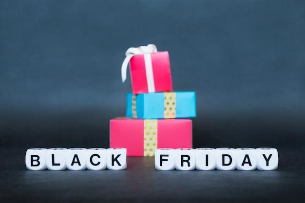 Banner de venta con texto de la palabra black friday y cajas de regalo multicolor.