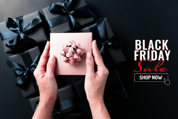 Banner de venta de viernes negro con mujer sosteniendo cajas de regalo