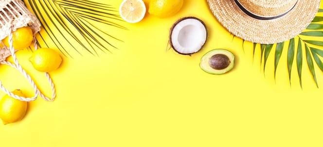 Banner de verano con sombrero de paja, hoja de palma, limones, coco y aguacate sobre un fondo amarillo. concepto de vacaciones