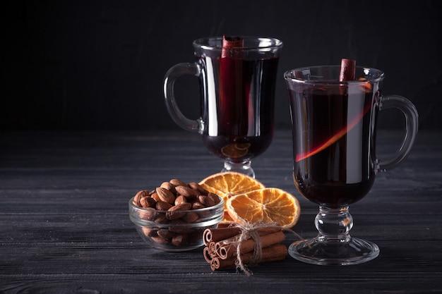 Banner de vino caliente. gafas con vino tinto caliente y especias sobre fondo oscuro.
