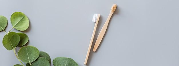 Banner web con cepillos de dientes de bambú natural eco plano sobre fondo gris