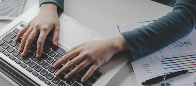 Banner web. mano en el teclado de una mujer joven escribiendo trabajando con una computadora portátil y un documento en el escritorio de la oficina