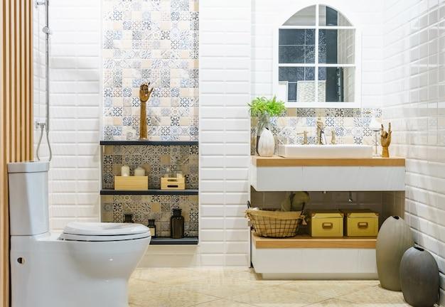 Baño amplio y moderno con azulejos brillantes con inodoro y lavabo. vista lateral