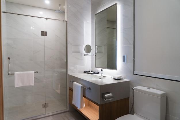 Baño contemporáneo iluminado con toallas limpias colgando de las manijas