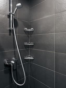 Baño inodoro y ducha en hotel con paredes grises y blancas