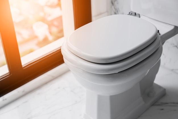 Baño interior de mármol blanco con detalle de armario de agua