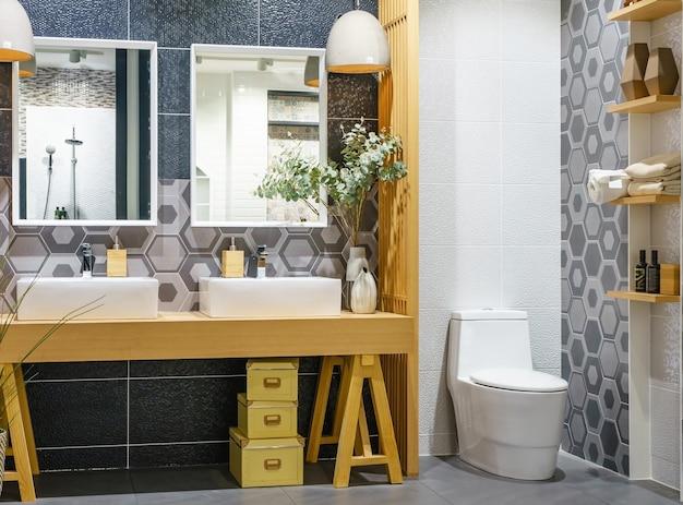 Baño luminoso y blanco con tocador de madera con un mostrador de azulejos.