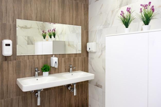 Baño minimalista con dos lavabos decorados con vegetación.