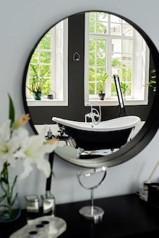 Baño moderno en blanco y negro con accesorios plateados con grandes ventanas soleadas, reflejo en el espejo. concepto de diseño de interiores