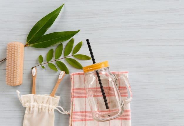 El baño y el objeto de desperdicio cero utilizan menos concepto de plástico / cepillo para el piso, cepillo de dientes de bambú en una bolsa de tela de algodón hoja verde