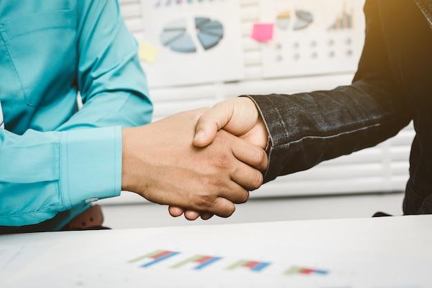 Banquero estrechándole la mano al cliente para aprobar el alquiler de una casa