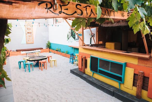 Bar de un hotel de playa con colores muy vivos junto a mesas y plantas.