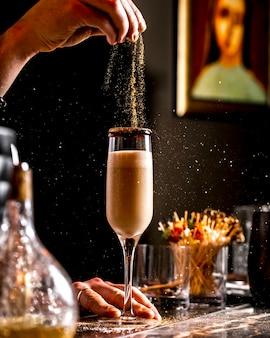 Bar tierna rocía brillo dorado en cóctel en copa de champán
