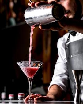 Bar tierna vierte un cóctel de una coctelera en una copa de martini