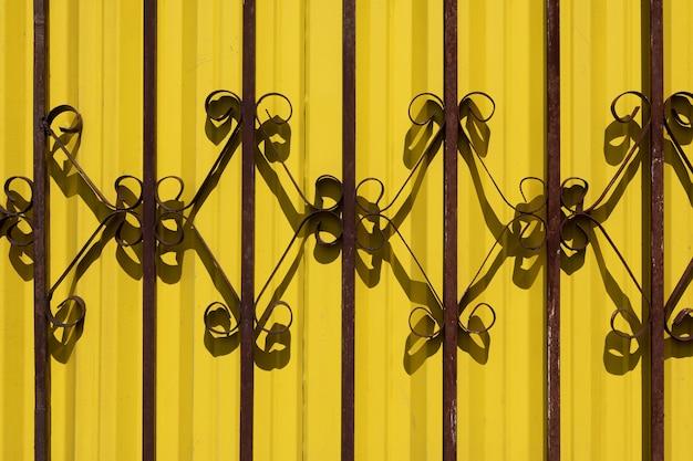 Barandilla de hierro forjado contra la pared amarilla vibrante