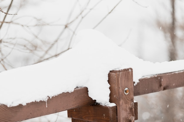 Barandilla de madera en bosque de invierno