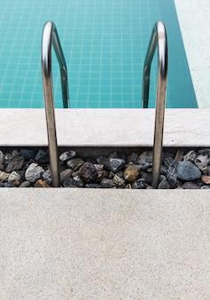 Barandilla de metal de la escalera en una piscina clara
