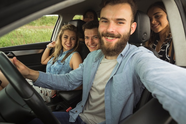 Barba joven sentado con su amigo en el coche tomando selfie