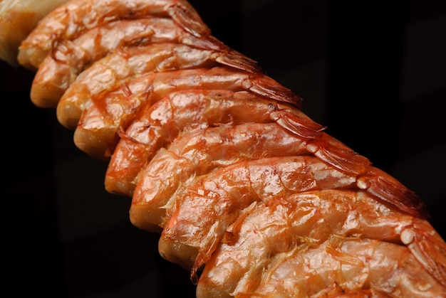Barbacoa de camarones en brochetas sobre fondo negro gastronomía brasileña