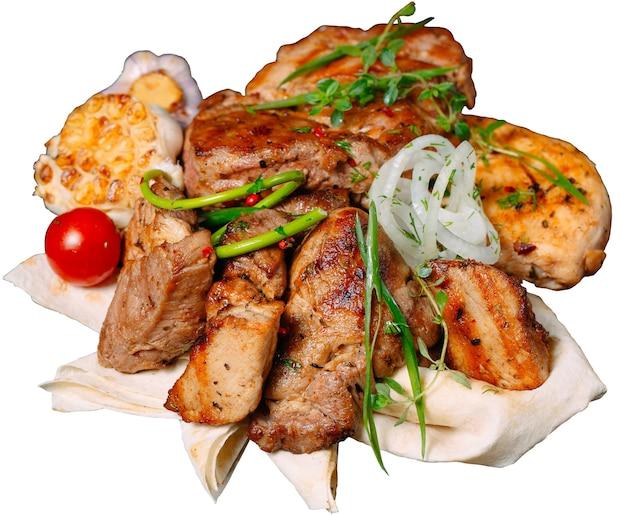 Barbacoa de carne con cebolla, pan de pita y hierbas aisladas sobre fondo blanco.