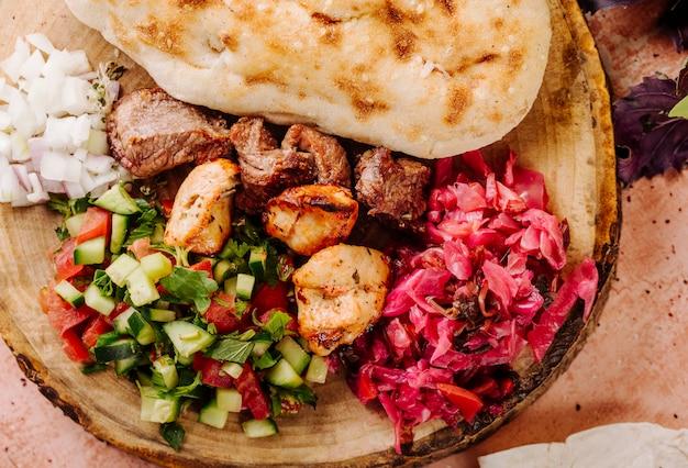 Barbacoa de carne con ensalada de verduras y repollo marinado en un trozo de madera.