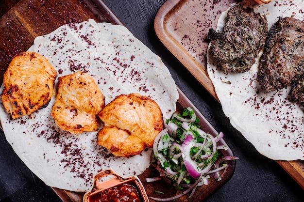 Barbacoa de carne y pollo en lavash con ensalada de cebolla y salsa barbacoa.