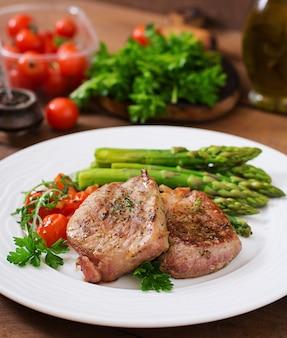 Barbacoa de carne de ternera a la parrilla con espárragos y tomates.