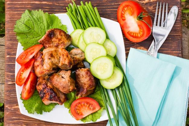 Barbacoa de carne y verduras frescas en un plato sobre una mesa de madera, vista superior
