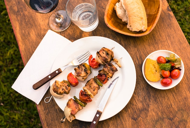 Barbacoa de carnes y verduras en mesa y copa de vino.