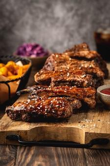 Barbacoa costillas de cerdo en una tabla de madera, papas gajo, hamburguesa y vaso de cola, sause. comida rápida. primer plano, copia espacio.